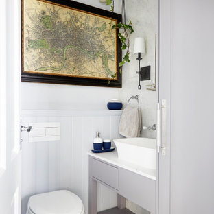 This is an example of a medium sized classic cloakroom in London with grey cabinets, a one-piece toilet, grey tiles, porcelain tiles, grey walls, porcelain flooring, quartz worktops, grey floors, white worktops, freestanding cabinets and a vessel sink.