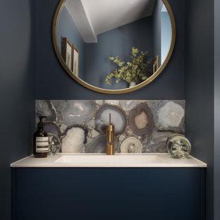 Свежая идея для дизайна: маленький туалет в современном стиле с плоскими фасадами, синими фасадами, разноцветной плиткой, серыми стенами, врезной раковиной и белой столешницей - отличное фото интерьера