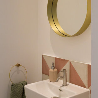 This is an example of a contemporary cloakroom in London with pink tiles and a wall-mounted sink.