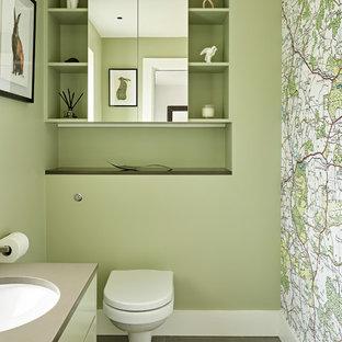 ロンドンのコンテンポラリースタイルのおしゃれなトイレ・洗面所 (フラットパネル扉のキャビネット、緑のキャビネット、壁掛け式トイレ、緑の壁、アンダーカウンター洗面器、グレーの床、グレーの洗面カウンター) の写真