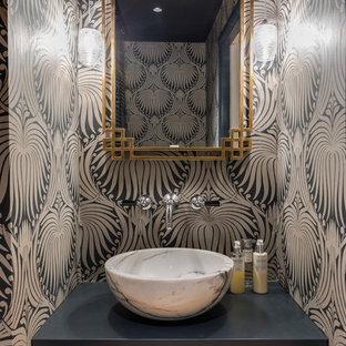 Modelo de aseo bohemio con lavabo sobreencimera, paredes multicolor y encimeras negras