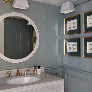 Idée de décoration pour un WC et toilettes tradition de taille moyenne avec un placard à porte plane, des portes de placard grises, un mur bleu, un lavabo encastré, un plan de toilette gris, meuble-lavabo encastré et boiseries.