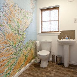 Стильный дизайн: туалет среднего размера в современном стиле с раковиной с пьедесталом, раздельным унитазом, керамогранитной плиткой, белыми стенами и полом из винила - последний тренд