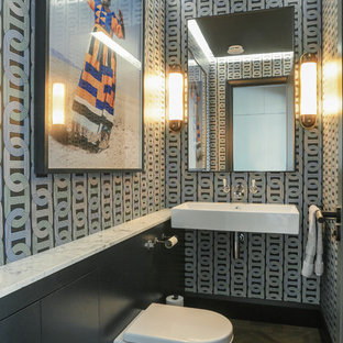 Inspiration for a contemporary cloakroom in London with a wall mounted toilet, multi-coloured walls, medium hardwood flooring, a wall-mounted sink and brown floors.