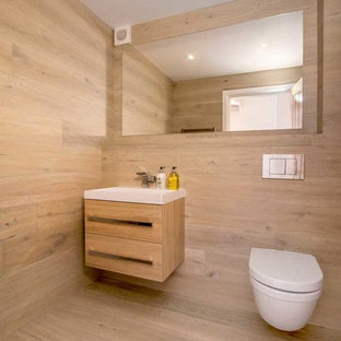 Design ideas for a contemporary cloakroom in Cheshire with flat-panel cabinets, light wood cabinets, a wall mounted toilet, light hardwood flooring and beige floors.
