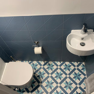 Small modern cloakroom in London with a one-piece toilet, blue tiles, grey walls, ceramic flooring, a wall-mounted sink and multi-coloured floors.