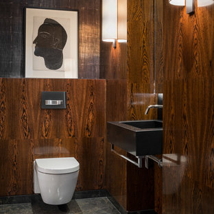 Contemporary cloakroom in London with a wall mounted toilet, brown walls, a vessel sink and grey floors.