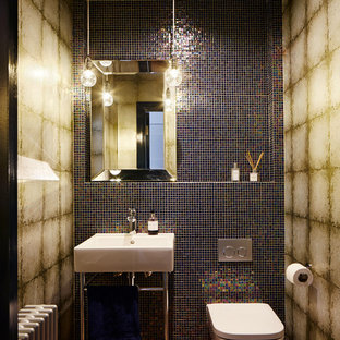 Small bohemian cloakroom in London with a wall mounted toilet, multi-coloured tiles, mosaic tiles, multi-coloured walls, a console sink and brown floors.