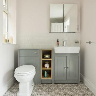 Idée de décoration pour un WC et toilettes tradition de taille moyenne avec un placard avec porte à panneau encastré, un WC à poser, un lavabo posé, des portes de placards vertess, un mur blanc et un plan de toilette en bois.
