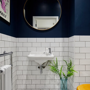 Inspiration for a small contemporary cloakroom in London with a one-piece toilet, white tiles, ceramic tiles, blue walls, ceramic flooring, a wall-mounted sink and multi-coloured floors.