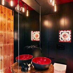 Пример оригинального дизайна: маленький туалет в современном стиле с плоскими фасадами, черными фасадами, инсталляцией, черной плиткой, черными стенами, полом из керамогранита, настольной раковиной, столешницей из дерева, красным полом и коричневой столешницей