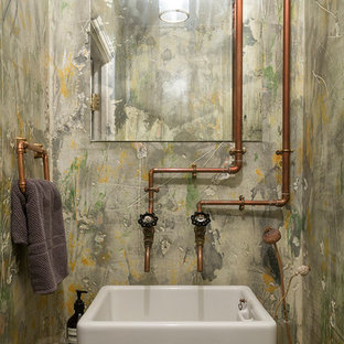 This is an example of an urban cloakroom in London with green walls, a vessel sink, wooden worktops and brown worktops.