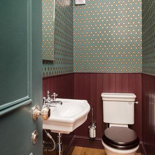 Неиссякаемый источник вдохновения для домашнего уюта: маленький туалет в классическом стиле с раздельным унитазом, светлым паркетным полом, подвесной раковиной, коричневым полом и разноцветными стенами