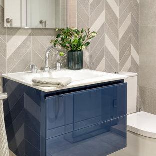 Ispirazione per un piccolo bagno di servizio design con ante lisce, ante blu, WC a due pezzi, piastrelle grigie, piastrelle di pietra calcarea, pareti grigie, pavimento in marmo, lavabo sospeso, pavimento bianco, top bianco e mobile bagno sospeso
