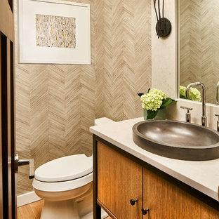 デンバーのラスティックスタイルのおしゃれなトイレ・洗面所 (フラットパネル扉のキャビネット、中間色木目調キャビネット、グレーのタイル、無垢フローリング、ベッセル式洗面器、茶色い床、白い洗面カウンター) の写真
