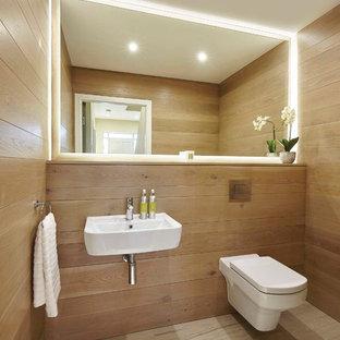 Réalisation d'un WC et toilettes design avec un WC suspendu, un mur marron, un lavabo suspendu et un sol beige.
