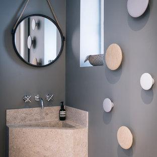 Idée de décoration pour un WC et toilettes design avec des portes de placard beiges, un mur gris, un lavabo intégré et un plan de toilette beige.