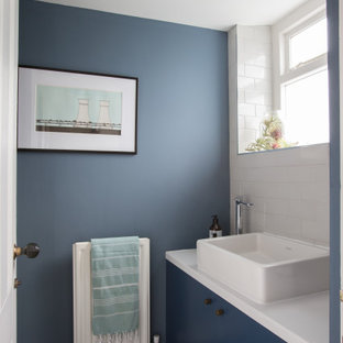 Design ideas for a small contemporary cloakroom in Other with flat-panel cabinets, blue cabinets, white tiles, metro tiles, blue walls, a vessel sink, multi-coloured floors, white worktops and a built in vanity unit.