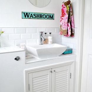 Klassisk inredning av ett toalett, med ett fristående handfat, luckor med lamellpanel, vita skåp, kaklad bänkskiva, en toalettstol med hel cisternkåpa, vit kakel och tunnelbanekakel