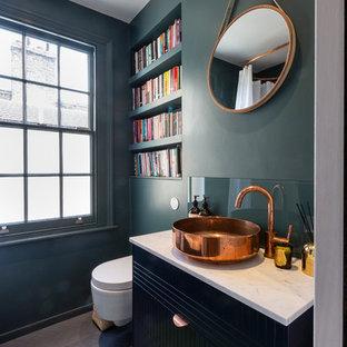 Moderne Gästetoilette mit flächenbündigen Schrankfronten, schwarzen Schränken, Wandtoilette, grüner Wandfarbe, dunklem Holzboden, Aufsatzwaschbecken, braunem Boden und weißer Waschtischplatte in London