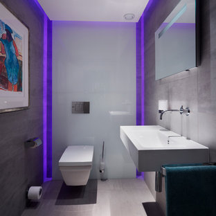Mid-sized contemporary powder room in Wiltshire with a wall-mount toilet, gray tile, porcelain tile, grey walls, porcelain floors and a wall-mount sink.