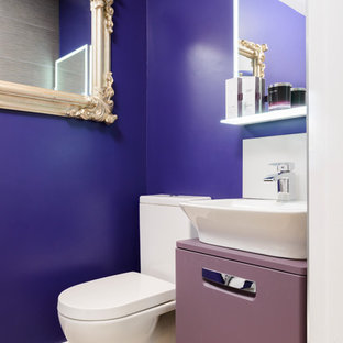 Cette photo montre un petit WC et toilettes éclectique avec un placard à porte plane, des portes de placard violettes, un mur violet et un plan de toilette violet.