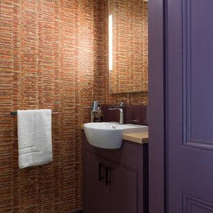 ロンドンのコンテンポラリースタイルのおしゃれなトイレ・洗面所 (フラットパネル扉のキャビネット、紫のキャビネット、オレンジの壁、オーバーカウンターシンク、木製洗面台) の写真