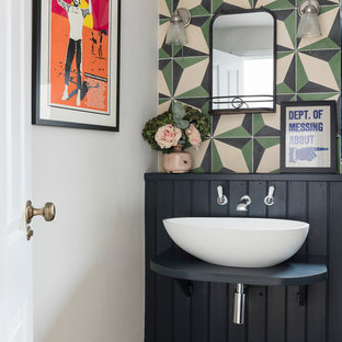 Eclectic powder room in Other with multi-coloured walls, a vessel sink, brown floor and black benchtops.
