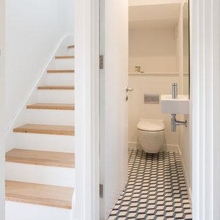 Foto di un piccolo bagno di servizio scandinavo con WC sospeso, pavimento con piastrelle in ceramica, lavabo sospeso, pavimento multicolore e pareti bianche