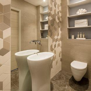 Aménagement d'un WC et toilettes contemporain de taille moyenne avec un lavabo intégré, un WC suspendu, un mur beige, un sol en carrelage de céramique, un carrelage beige et des portes de placard en bois clair.