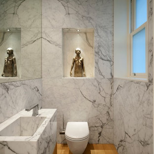 Photo of a small contemporary cloakroom in London with an integrated sink, a wall mounted toilet, medium hardwood flooring, marble worktops, grey walls and marble tiles.