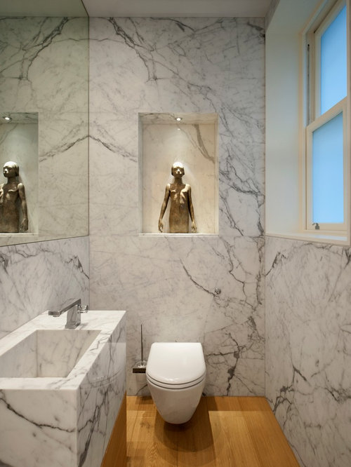 Powder room - small contemporary marble tile medium tone wood floor powder  room idea in London