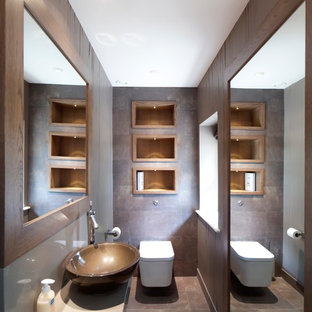 Design ideas for a contemporary cloakroom in Gloucestershire with a vessel sink, a wall mounted toilet and brown tiles.