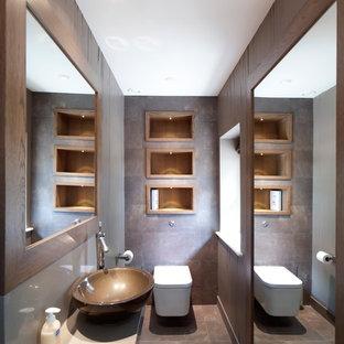 Idee per un bagno di servizio minimal con lavabo a bacinella, WC sospeso e piastrelle marroni
