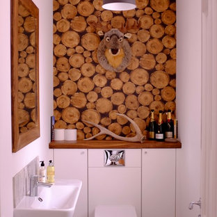 This is an example of a rustic cloakroom in Hampshire with flat-panel cabinets, white cabinets, a wall mounted toilet, grey tiles, white walls, a wall-mounted sink, wooden worktops and grey floors.