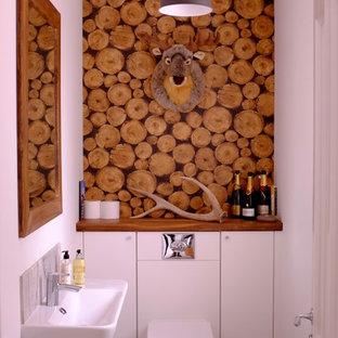 Cette photo montre un WC et toilettes montagne avec un placard à porte plane, des portes de placard blanches, un WC suspendu, un carrelage gris, un mur blanc, un lavabo suspendu, un plan de toilette en bois et un sol gris.