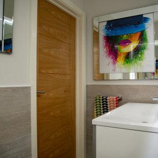 Idée de décoration pour un petit WC et toilettes design avec un placard à porte vitrée, des portes de placard blanches, un WC suspendu, un carrelage gris, des carreaux de porcelaine, un mur gris, un sol en carrelage de porcelaine, un lavabo suspendu et un sol gris.