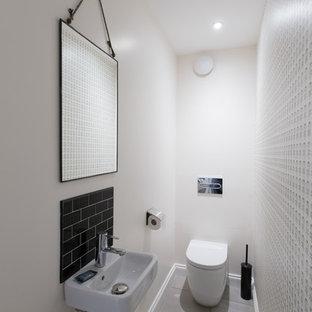 Modelo de aseo escandinavo, pequeño, con sanitario de una pieza, baldosas y/o azulejos negros, baldosas y/o azulejos de cerámica, paredes blancas, suelo de linóleo y lavabo suspendido