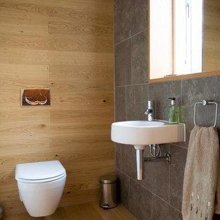 Inspiration för ett litet funkis toalett, med ett väggmonterat handfat, en vägghängd toalettstol, porslinskakel, ljust trägolv och grå kakel