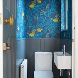 Small classic cloakroom in London with a two-piece toilet, blue walls, a wall-mounted sink and grey floors.
