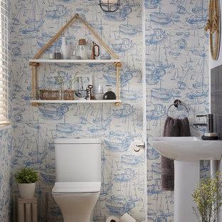Bild på ett litet maritimt toalett, med en toalettstol med hel cisternkåpa, grå kakel, orange kakel, porslinskakel, blå väggar, klinkergolv i keramik och ett piedestal handfat