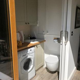 Свежая идея для дизайна: маленький туалет в современном стиле с плоскими фасадами, белыми фасадами, инсталляцией, бежевой плиткой, керамической плиткой, белыми стенами, полом из ламината, накладной раковиной, столешницей из дерева, коричневым полом и коричневой столешницей - отличное фото интерьера
