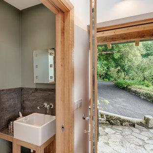 Inspiration pour un petit WC et toilettes design avec un placard en trompe-l'oeil, des portes de placard en bois clair, un WC suspendu, un carrelage gris, des carreaux de céramique, un mur vert, un sol en calcaire, une grande vasque, un plan de toilette en carrelage et un sol beige.