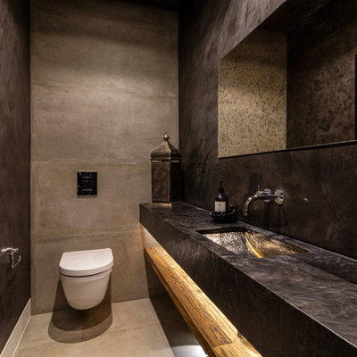 Mid-sized tuscan concrete floor and gray floor powder room photo in West Midlands with a wall-mount toilet, black walls and a wall-mount sink