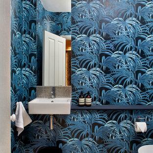Aménagement d'un petit WC et toilettes contemporain avec un WC suspendu, un mur bleu, un sol en bois clair, un placard sans porte, un lavabo suspendu, un plan de toilette en bois, un sol beige et un plan de toilette bleu.