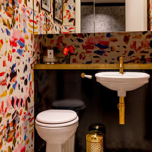 Design ideas for a small eclectic cloakroom in London with black cabinets, a one-piece toilet, multi-coloured tiles, multi-coloured walls, ceramic flooring, a wall-mounted sink, wooden worktops, black floors and black worktops.