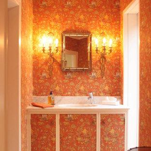 Cette photo montre un grand WC et toilettes éclectique avec un placard à porte plane, des portes de placard oranges, un mur orange, un sol en marbre, un lavabo encastré, un plan de toilette en marbre, un sol gris et un plan de toilette blanc.