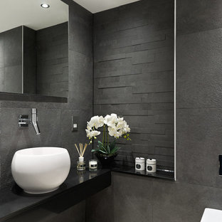 Inspiration for a contemporary cloakroom in Surrey with a vessel sink, a wall mounted toilet, grey tiles, black tiles and grey walls.