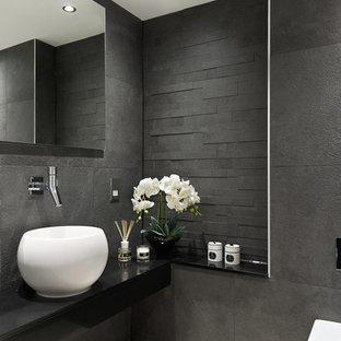 Идея дизайна: туалет в современном стиле с настольной раковиной, инсталляцией, серой плиткой, черной плиткой, серыми стенами и черной столешницей