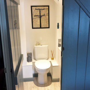 Пример оригинального дизайна: маленький туалет в стиле рустика с раздельным унитазом, черно-белой плиткой, цементной плиткой, белыми стенами и раковиной с несколькими смесителями